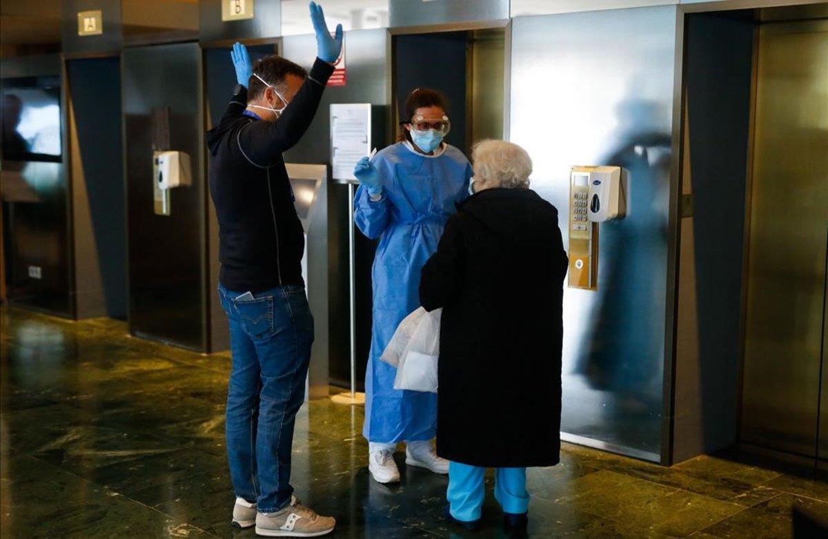 El director del hotel, Enrique Aranda, a la izquierda, y una sanitaria atienden a una paciente en la recepción.