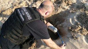 Un agente de los Tedax, con el artefacto hallado en la playa de la Arrabassada de Tarragona, este lunes.