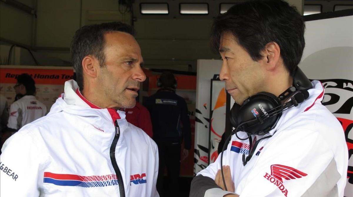 Alberto Puig, vestido con el uniforme de Honda, conversa con el japonés Tetsuhiro Kuwata, director de operaciones de la fábrica japonesa.