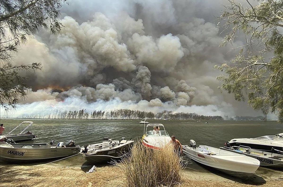 Barcos en la orilla del lago Conjola, cuyos alrededores están amenazados por el fuego.