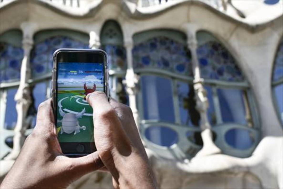 Un usuario de Pokémon Go juega frente a la Casa Batlló de Barcelona, un día antes de la salida oficial de la aplicación en España.