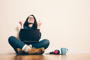 Chica joven contenta con ordenador portátil.