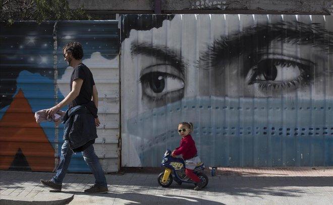Grafiti de una mujer con mascarilla en una calle del barrio de la Bonanova, en Barcelona.