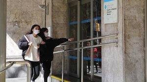 Dos chicas con mascarilla, por el riesgo de coronavirus, frente al CAP Manso, en Barcelona.