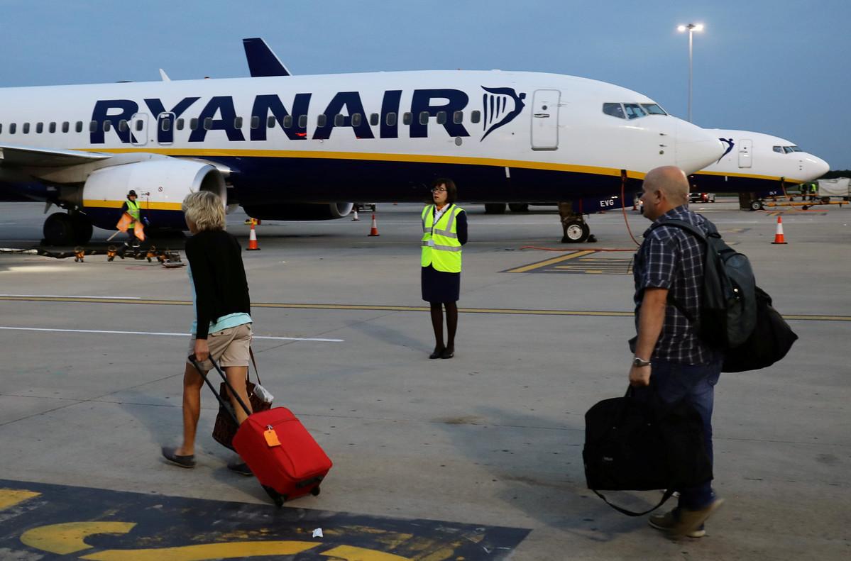 Pasajeros se dirijen a un avión de la compañia Ryanair en un aeropuerto de Londres