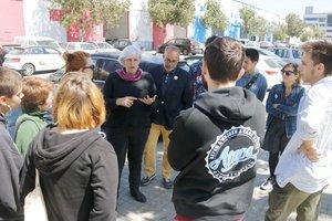 La candidata de Guanyem Badalona, Dolors Sabater, con su número 2, Oriol Lladó, en el polígono de Can Ribó con un grupo de jóvenes.