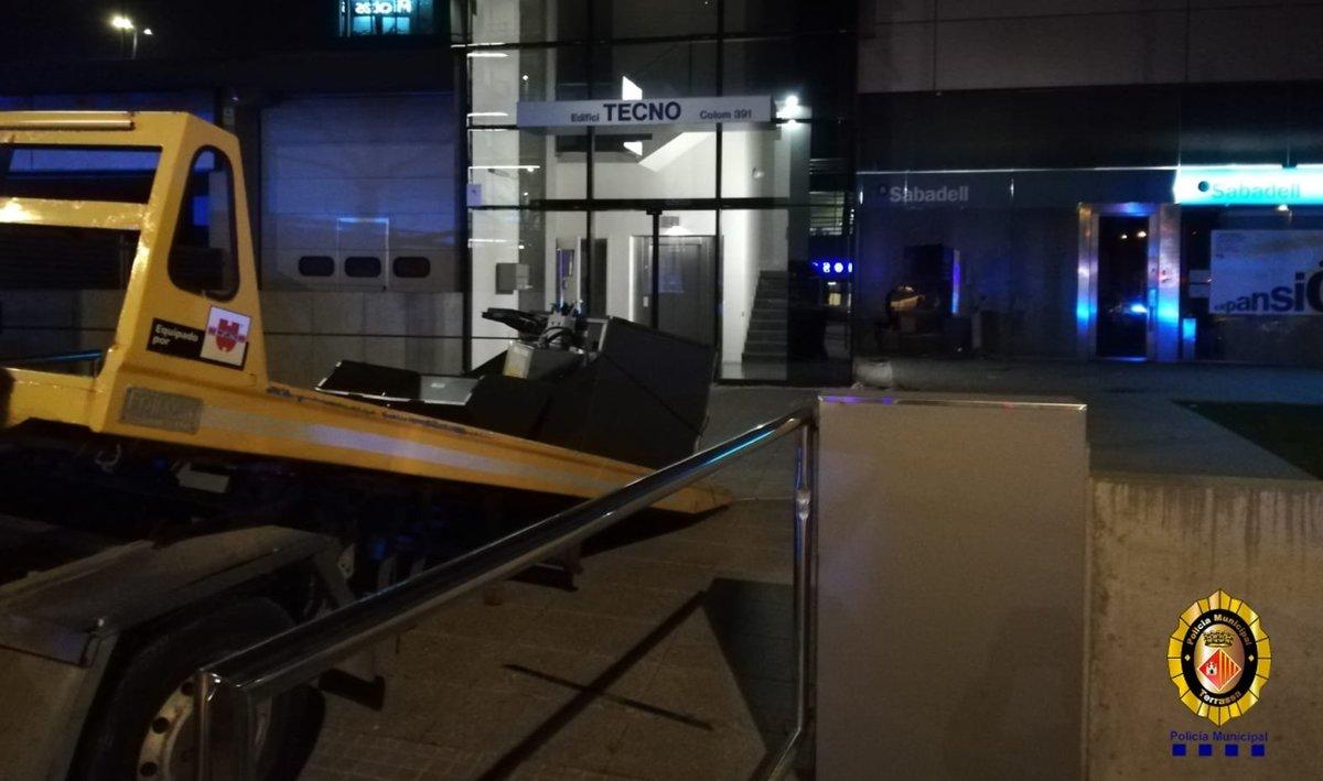 Grúa encastada contra una entidad bancaria en Terrassa.