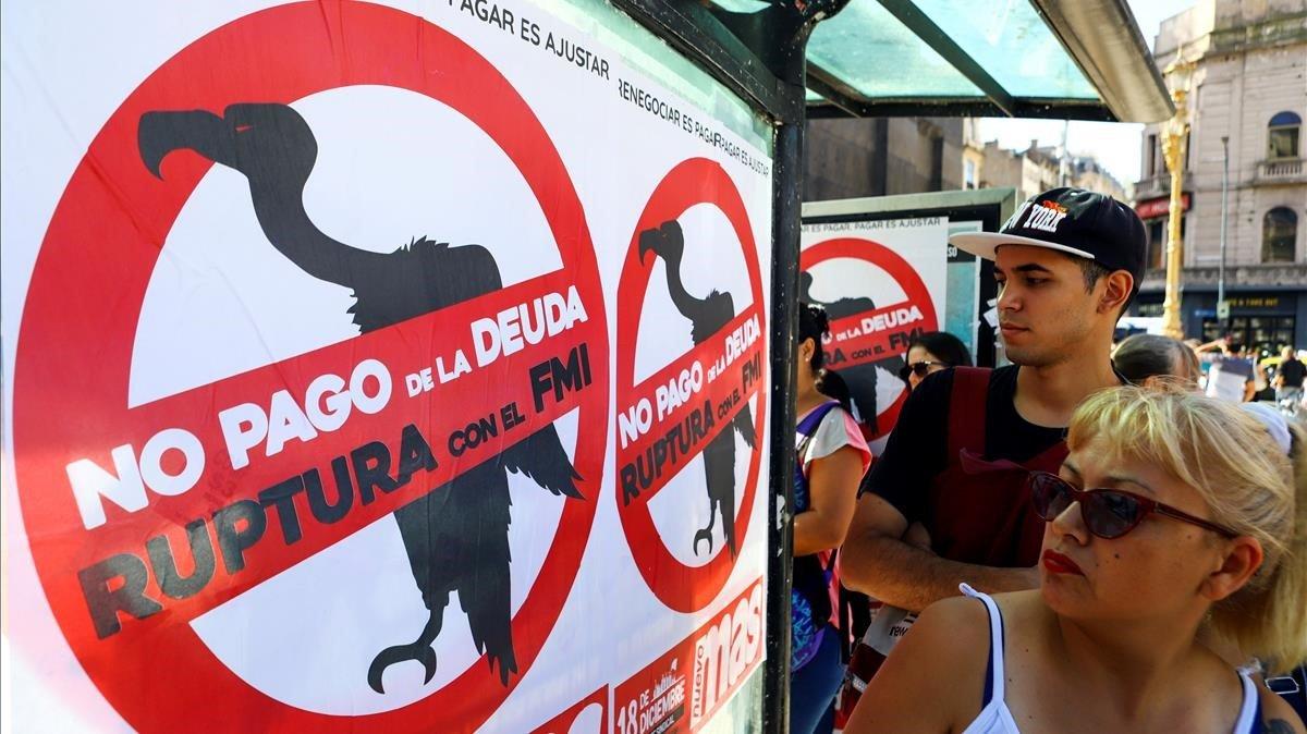 Un grupo de personas pasan junto a un cartel que pide al Gobierno argentino no pagar la deuda al FMI, en Buenos Aires.