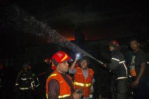 Bomberos trabajan para apagar el fuego en el area de Churihatta en Chawkbazar, Bangladés.