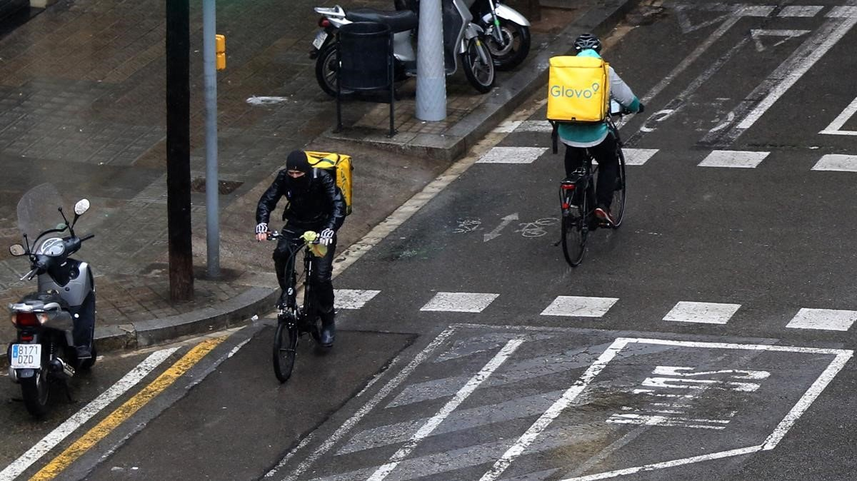 Dos 'riders' de Glovo, circulando bajo la lluvia por la calle de Provença, el pasado 16 de marzo.