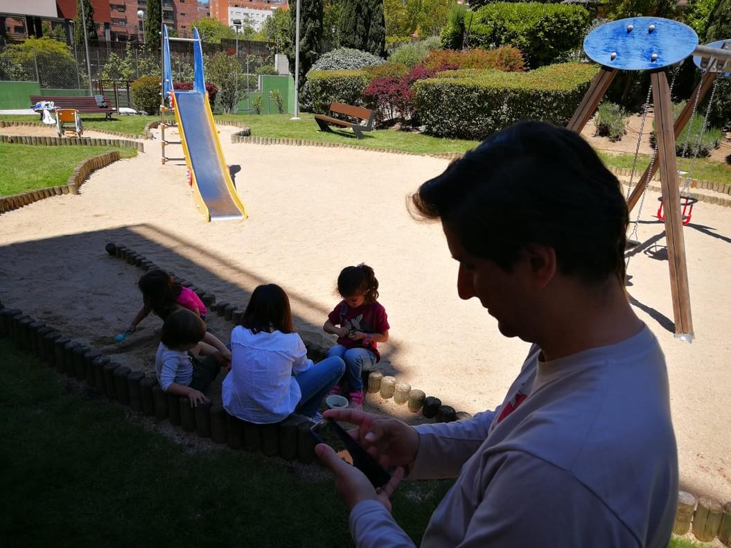 Un padre mira su móvil mientras sus dos hijas juegan con dos amigos en un parque cercano a su casa, en Madrid.