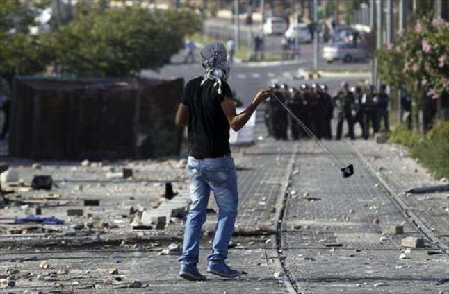 Un joven lanza piedras en una protesta en un suburbio árabe de Jerusalén.