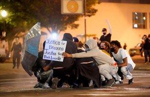 Manifestantes en el suelo intentar repeler el ataque congas pimienta enLouisville, Kentucky.