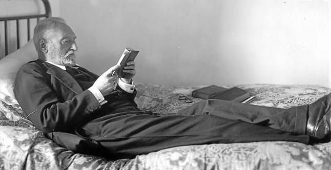 Miguel de Unamuno, amb un posat estudiat, llegeix estirat al llit, al seu domicili del carrer de Bordadores, a Salamanca.