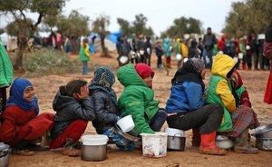 Niños esperan a recibir alimentos en el campo de refugiados sirio de Yazi Bagh.