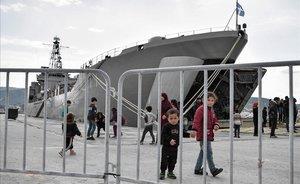Niños, junto al buque militar que acoge a los refugiados y migrantes que llegaron a la isla de Lesbos en marzo.
