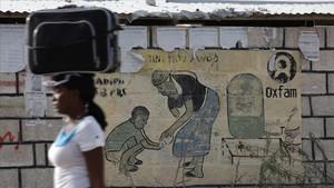 Una mujer pasa frente a una pared con una pintura de Oxfam en un campode desplazados tras el terremoto del 2010.
