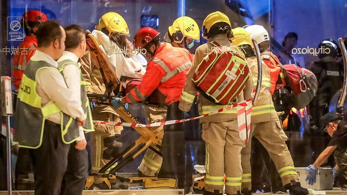 Personal sanitario traslada a una de las persona heridas en una sangrienta pelea con cuchillos en un centro comercial en Hong Kong, este domingo.