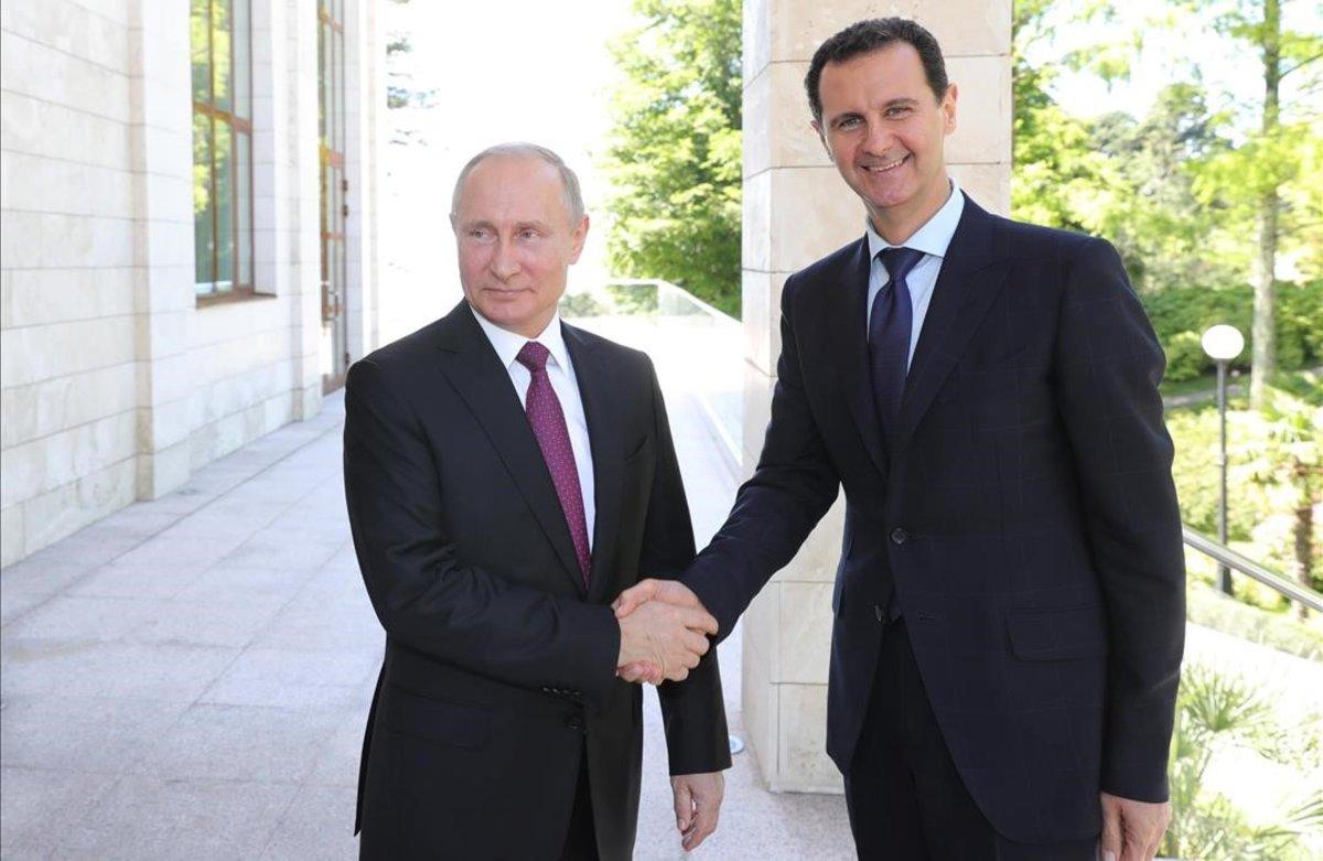 El presidente ruso, Vladímir Putin, y su homólogo sirio, Bashar al Asad, se saludan durante un encuentro en Sochi (Rusia) el pasado mayo.