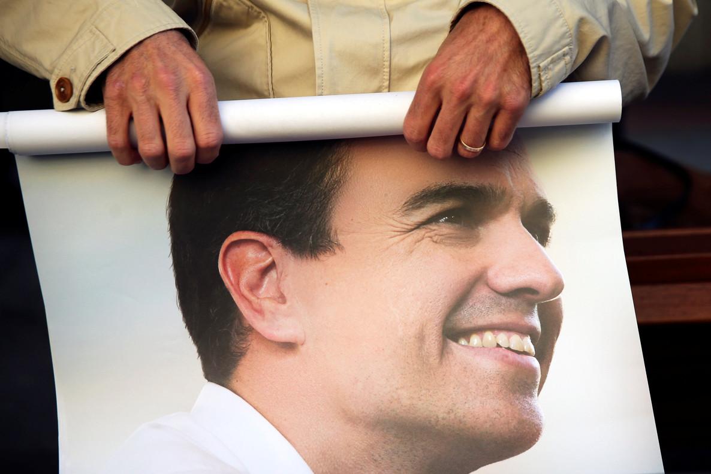 Un seguidor de Sánchez enrolla un cartel del ya exsecretario general del PSOE.