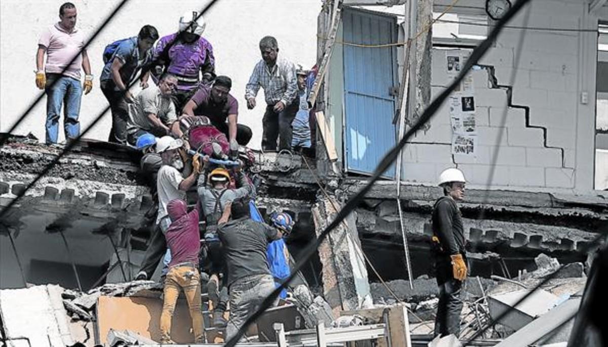 Una mujer es evacuada de uno de los edificios destruidos por el terremoto en la capital de México, ayer.