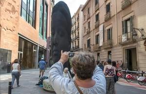 Una turista fotografía a Carmela, la escultura de Jaume Plensa que maravilla a los visitantes ante el Palau de la Música.