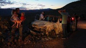 Varios miembros de la comunidad LeBarón inspeccionan uno de los vehículos atacados, este martes.