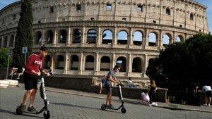Vecinos de Roma pasean por el exterior del Coliseo.