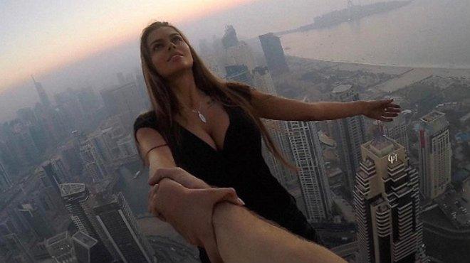 Viki Odintcova, de la mano de su asistente, sin arnés, a 300 metros de altura, a punto de hacerse un selfi de vértigo.