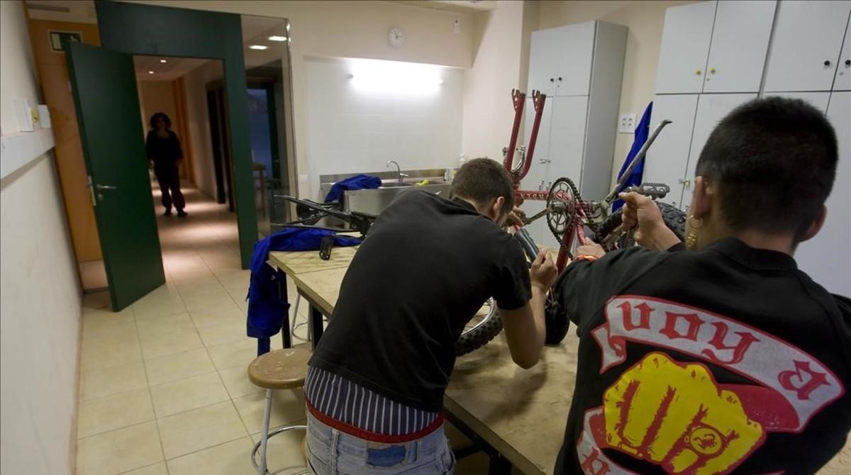 Dos chicos participan en un taller de reparación de bicicletas en el Casal dels Infants en el 2010.