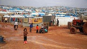 Los niños se reúnen fuera de sus refugios improvisados después de una lluvia torrencial que afectó a un campamento para personas desplazadas cerca de la ciudad de Atme, cerca de la frontera con Turquía, en la provincia de Idlib, al nortede Siria.
