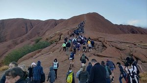 Una multitud de turistas hace cola para subir al monte Urulu, en Australia, este miércoles.