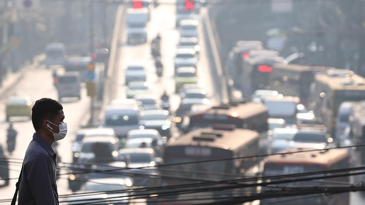 Un ciudadano tailandés camina por unas calles de Bangkok tapadas por la contaminación.