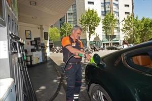 Un empleado llena un depósito en una gasolinera de Barcelona.