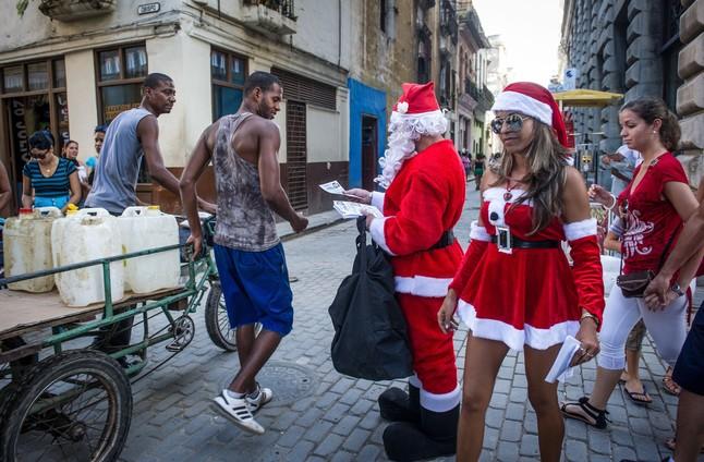 Unos cubanos vestidos de Papá Noel reparten folletos de un restaurante en La Habana.