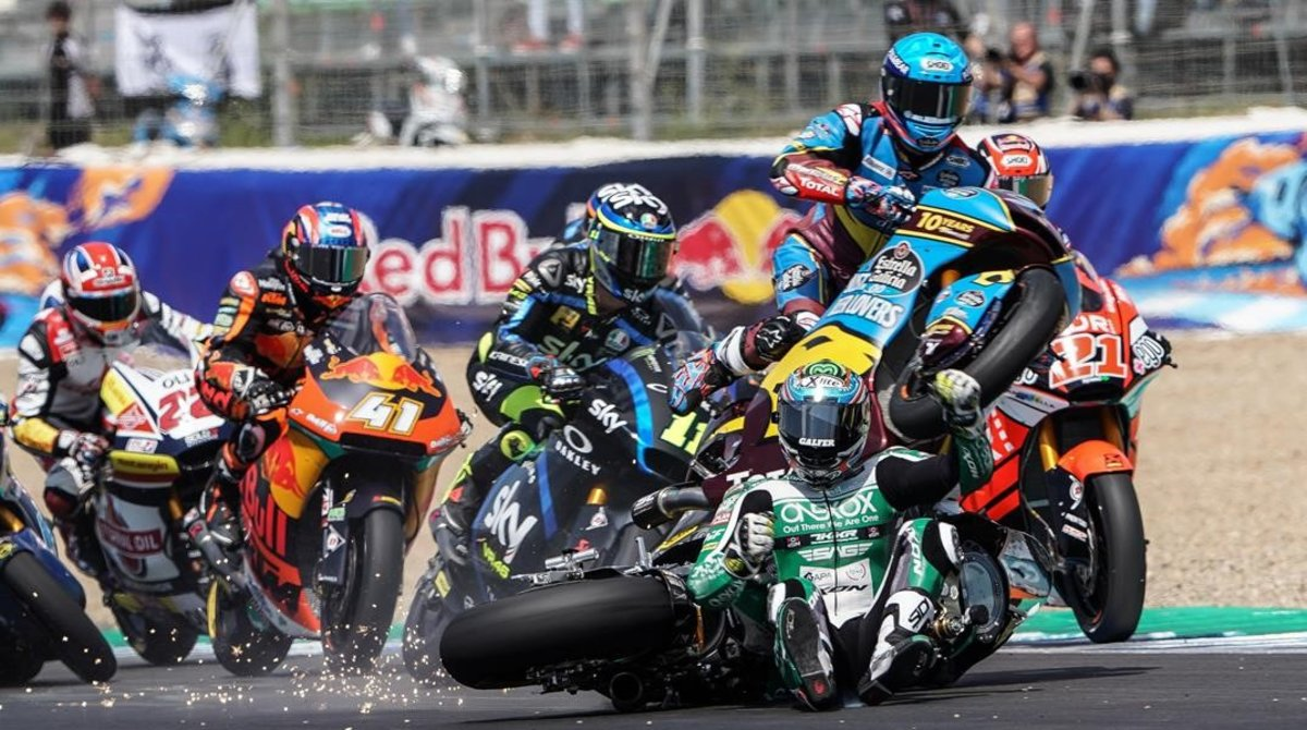 Àlex Márquez (Kalex), a la derecha, con casco azul, salta, vuela, por encima de la moto y el cuerpo del australiano Remy Gardner, sentado ya en la pista tras su caída, en la salida de hoy de Moto2, en Jerez.