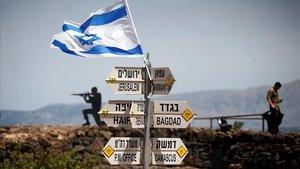 Un soldado israelí junto a un grupo de carteles que indican las distancias entre los Altos del Golán y varias ciudades de Oriente Próximo.