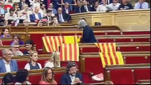 La diputada de Catalunya Sí que es Pot Àngels Martínez retira las banderas de España que habían dejado en su escaño los diputados del PP.