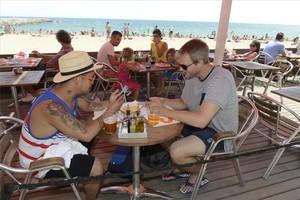 Dos turistas utilizan el móvil en una playa de Barcelona.