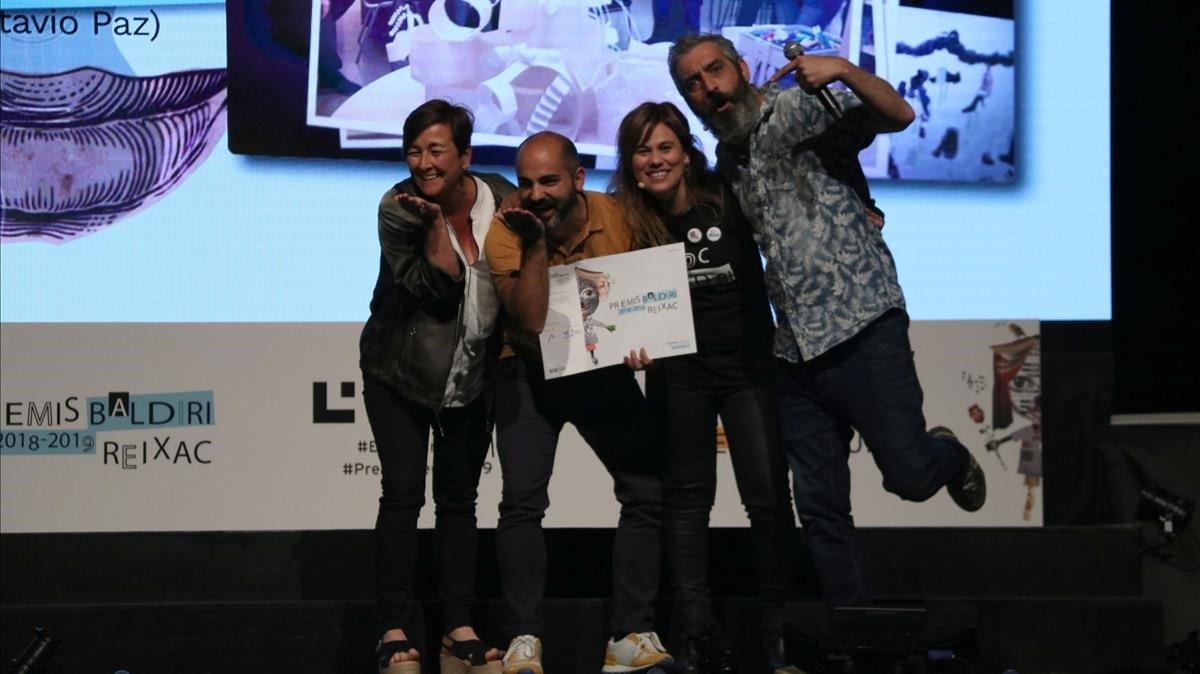 Elena Guillén y Xavi López, jefe de estudios y director de la escuela Octavio Paz, con el premio, junto a los presentadores Marta Esteve y Roger de Gràcia.