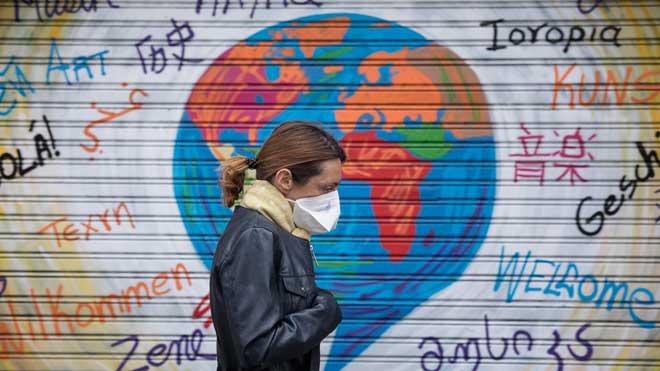 España supera a China en el número de fallecidos por coronavirus. En la foto, una mujer con mascarilla por la calle, en Barcelona.