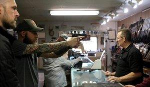 Un hombre sostiene una pistolaen una tienda de armas en Cheyenne, Wyoming, ante el temor al caos por la propagación del coronavirus.