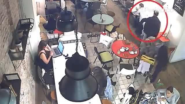 Un carterista entra en una cafetería de Barcelona, se sienta tras un cliente, simula rebuscar en su chaqueta pero en realidad le robala cartera a la víctima que está a su espalda.