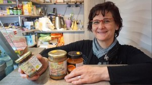 Mari Díaz, propietaria del puesto Herbolari Montserrat, junto a las mermeladas que vende en el mercado de Sants