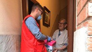Un miembro de la Cruz Roja entrega leche a un ciudadano mayor.