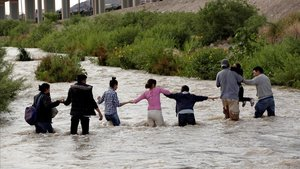 Imagen de archivo de un grupo de migrantes de Centroamérica formando una cadena humana para cruzar el Río Bravo y entrar en Estados Unidos.