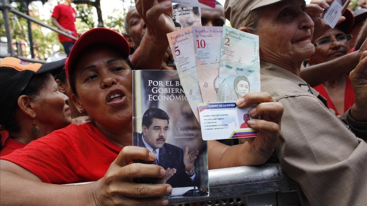 Una seguidora de Maduro muestra la nueva moneda venezolana.