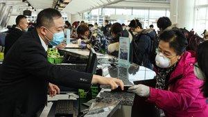 Pasajeros y personal en un aeropueto protegidos con mascarillas por el coronavirus.