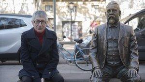 Oscar Abril Ascaso posa junto a la escultura que recuerda al urbanista que da nombre a esta plaza de Gràcia.