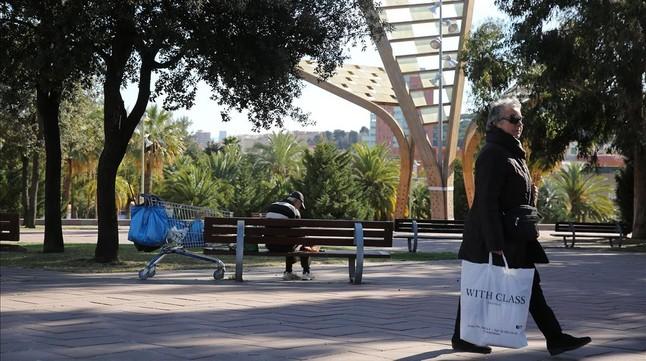 Una persona sin hogardescansa en el banco de la plaza de Karl Marx de Barcelona.